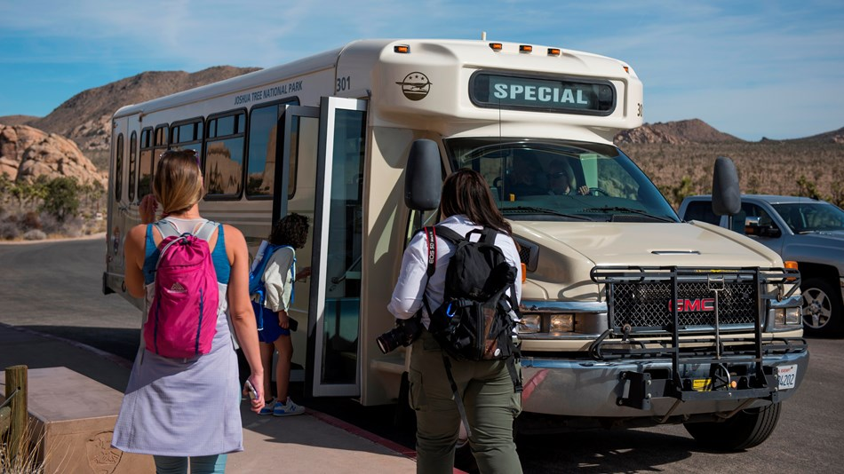 Color photo of visitors boarding the free RoadRunner shuttle bus.