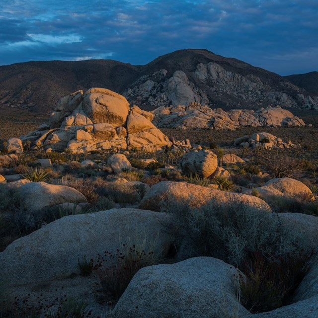 Low light on boulder piles with a dark cloudy background.