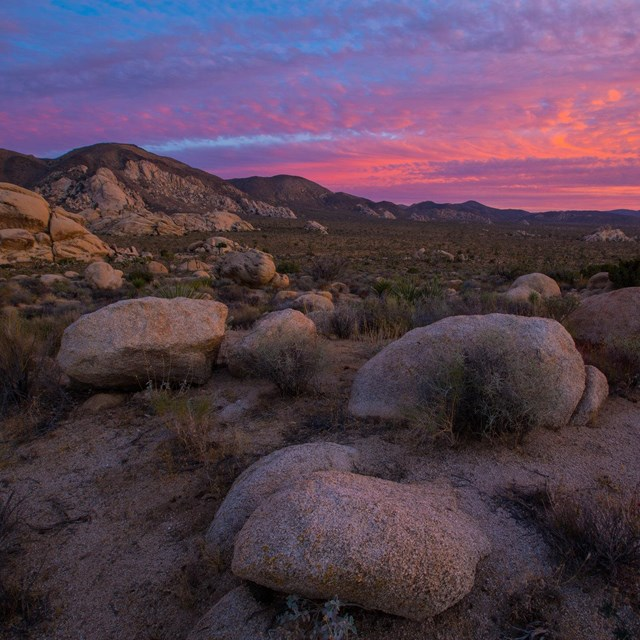 Color photo of vibrant sunset colors in the clouds with monzogranite boulders in the foreground.