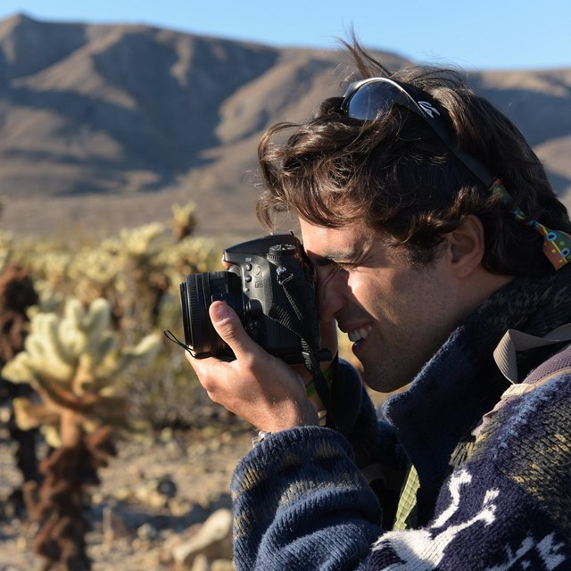 A young man holds a DSLR camera to his face and points it at cholla cacti.