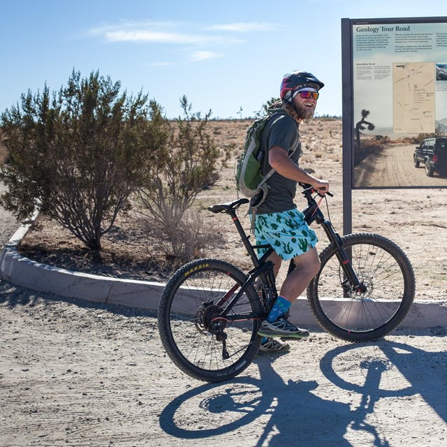 A mountain biker is stopped looking at the information panel about Geology Tour Road.