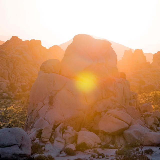 Large granite boulder piles backlit by a setting sun.