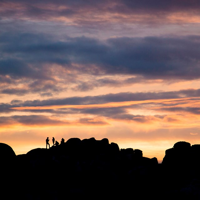 Four individuals atop rock formations silhouetted against a colorful sunset sky.