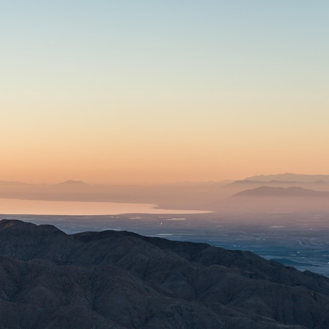 Color photo of sunrise as seen from Keys View looking out over the Salton Sea. It is very hazy/pink.