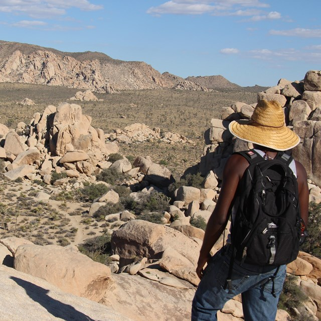 a hiker standing high on a rock outcrop looks over a desert valley