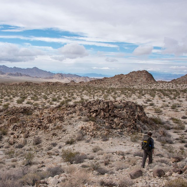 Color photo of a backpacker hiking through the Coxcomb Mountains.
