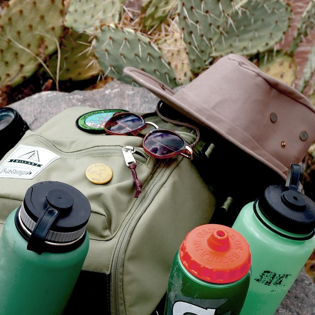 a backpack with water bottles, a hat, and sunglasses