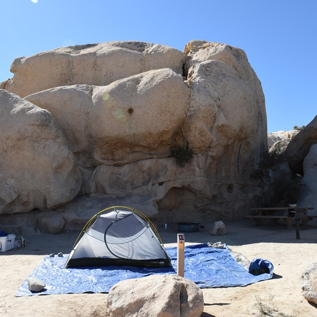 Color photo of a tent site set up in the shadow of a large rock formation. NPS / Hannah Schwalbe