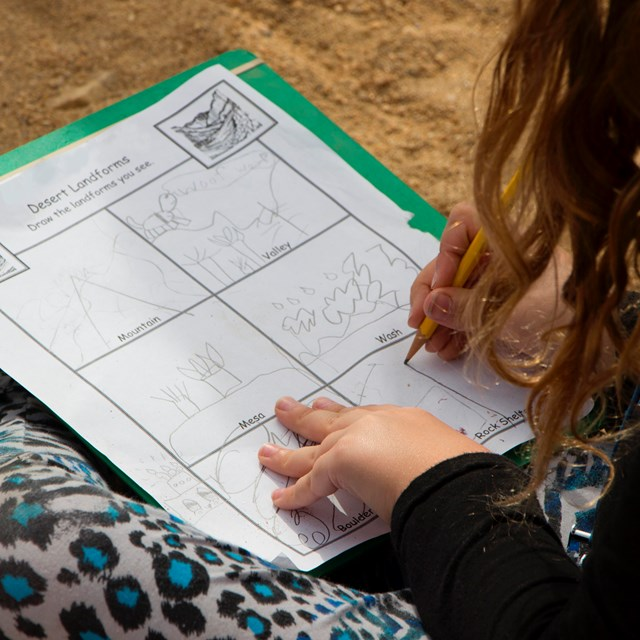 a child sitting on the ground draws desert landforms on a worksheet