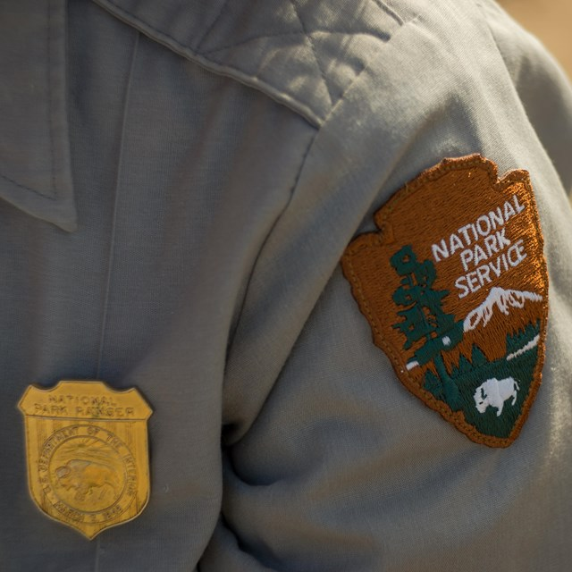 closeup of a park ranger's uniform showing official badge and patch