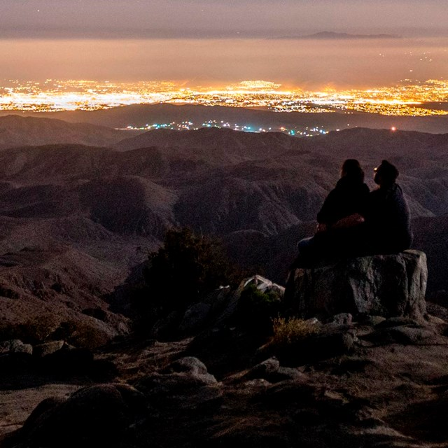 a couple sitting at a viewpoint at night, looking toward the lights of the Coachella Valley
