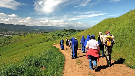 Visitors in period costumes hike along a scenic trail.
