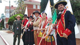 A park ranger and people in colorful costume hold flags at the Presidio of San Francisco