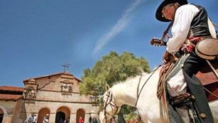 A rider sits mounted on a horse outside Mission San Antonio