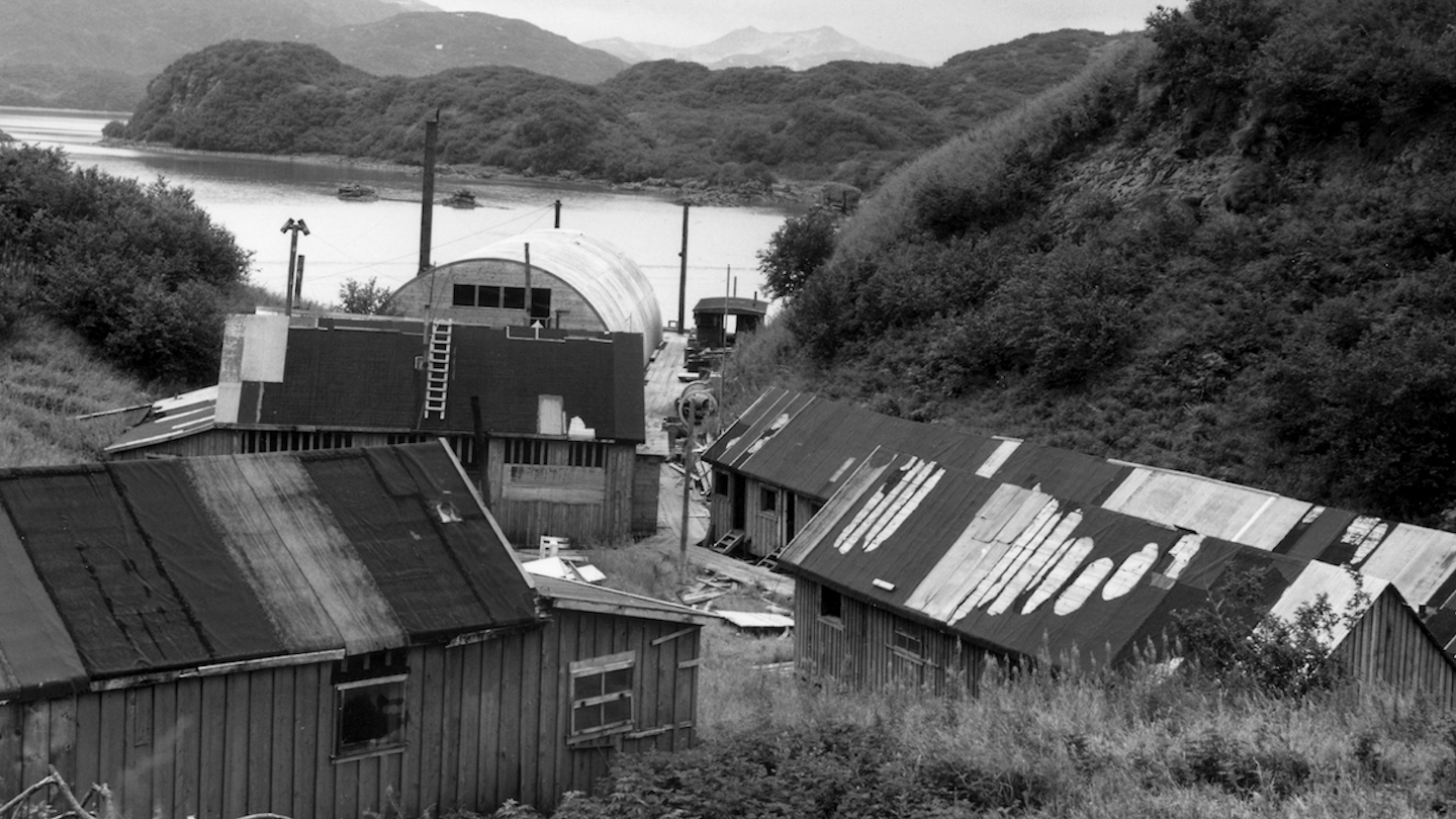 A black and white photograph of a collection of cannery buildings by a bay.