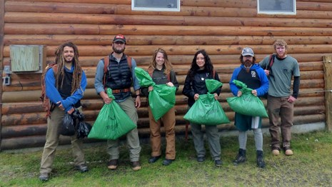 Student Conservation Crew holding garbage bags full of invasive plants.