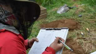 A scientist takes notes in the field