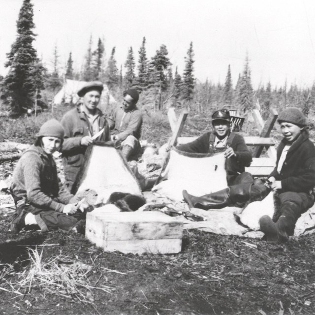A historic photo of six people at a camp site.
