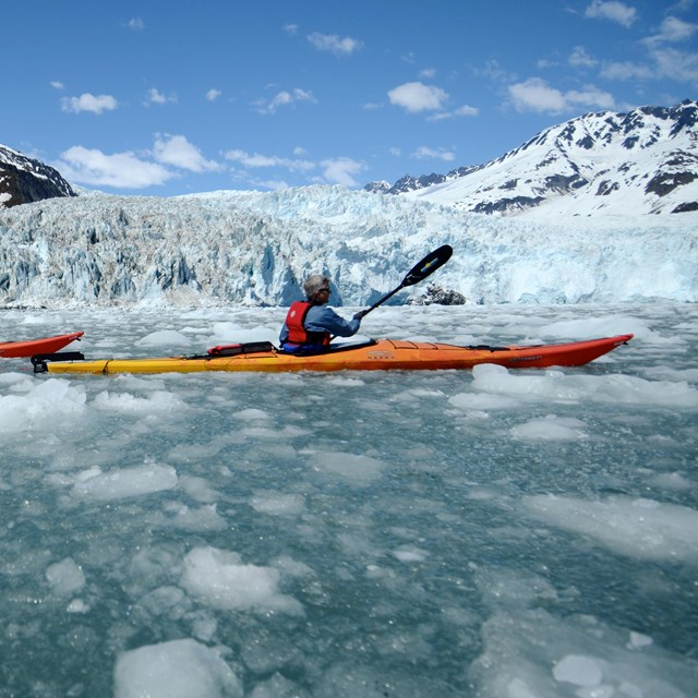 Two kayakers paddle through ice chunks from the background glacier.