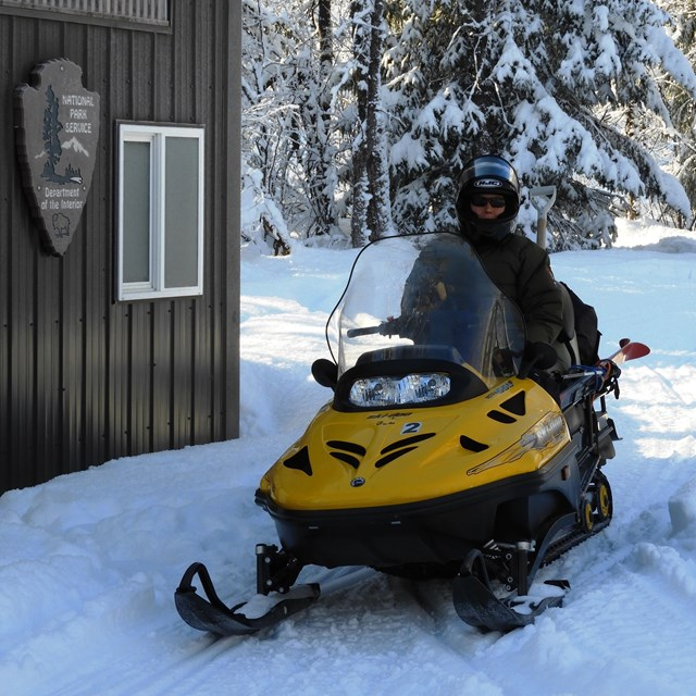 A park ranger sits on a snowmobile in front of a shed.