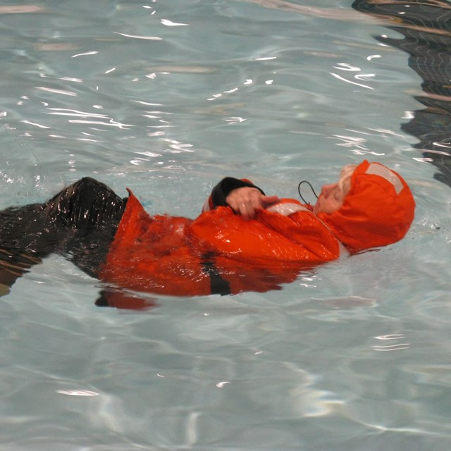 A person in an orange survival suit floats in the water.
