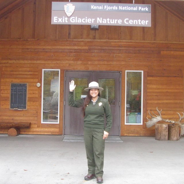 A park ranger waves in front of the Exit Glacier Nature Center.