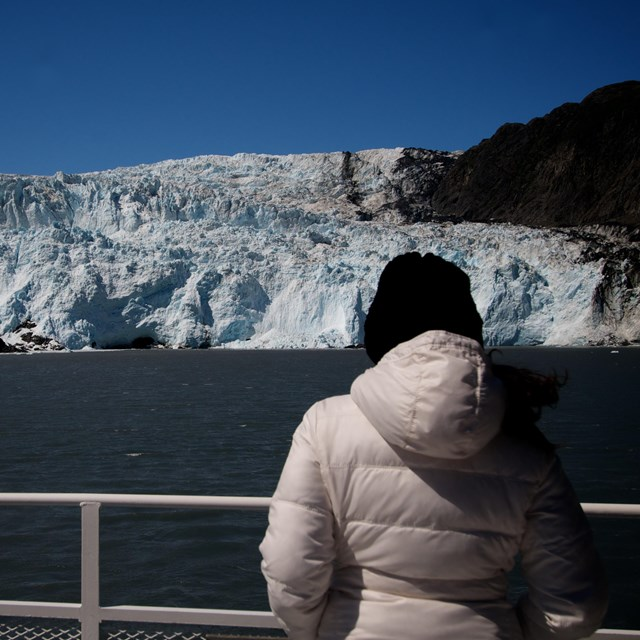 A woman looks at a tidewater glacier from the rail of a tour boat.