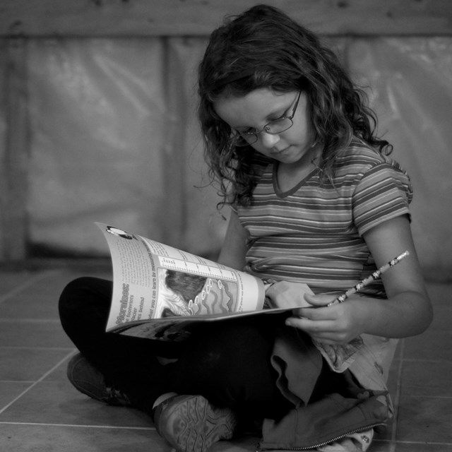A child sits on the floor looking at a book.