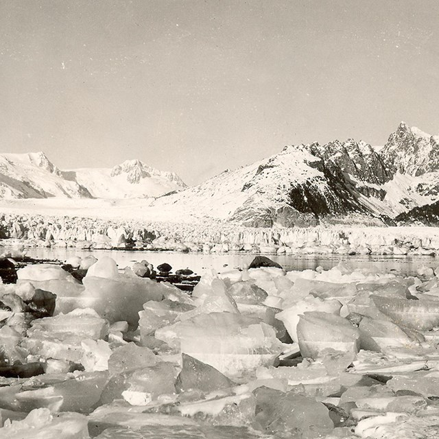 A black and white photo.  Chunks of ice are in the foreground of the image. d