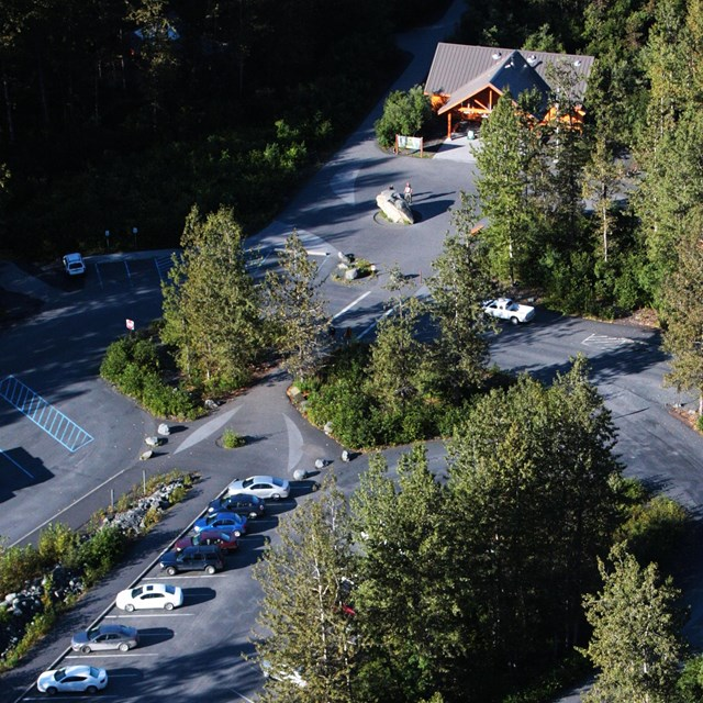 Aerial view of the Exit Glacier Visitor Center and Parking Area with green forest surrounding.