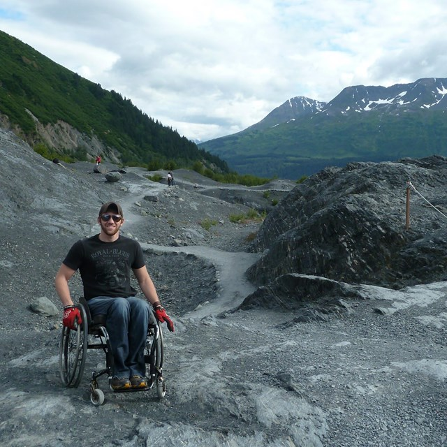 Man in a wheel chair on mountainous rocky area with trail in the background (Edge of Glacier Trail).