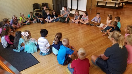 Students sit in a circle on a wood floor listening to a park ranger talk.