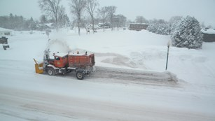 A snow-go machine removes snow along a street.