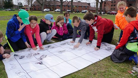 A group of students work on planning a community together.
