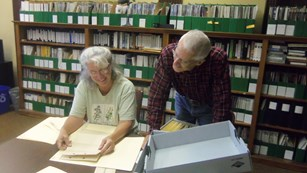 Two volunteers sort through archival materials inside of a library.