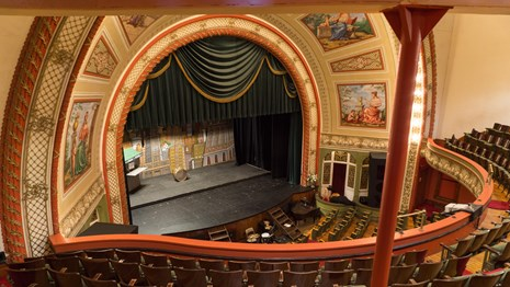 Interior of theatre from second balcony looking down at large stage framed by proscenium arch.