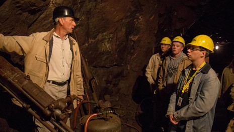 A tour guide with a hard hat talks to a group of youth with hard hats on about a drill used to mine.