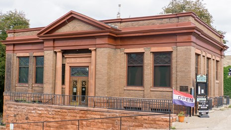 Exterior image of a historic Carnegie Library with two pillars.