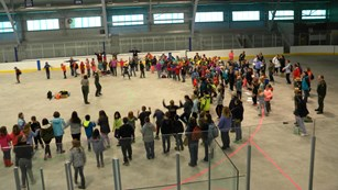 A large group of people stand in a half-circle on an indoor ice rink.