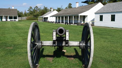 A historic cannon is facing the viewer with buildings in the background.