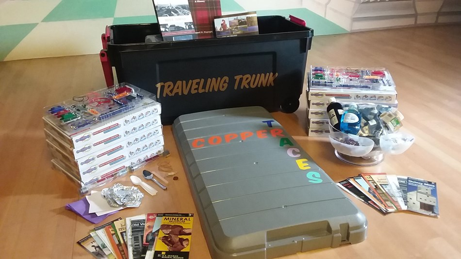 An assortment of items like snap circuit sets and brochures surround a trunk.