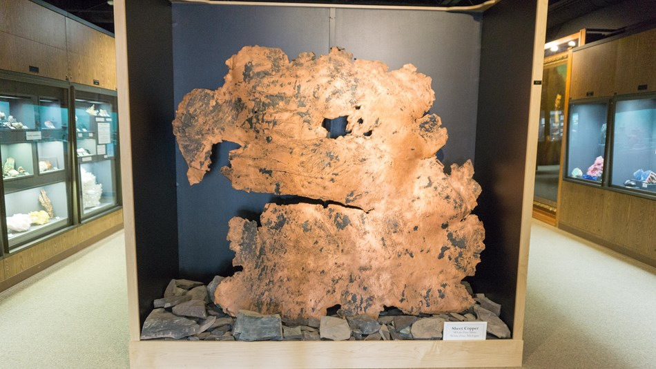 A large piece of copper is displayed inside of a museum.