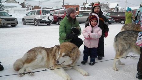 A sled dog lays on the ground and young children stand next to it.