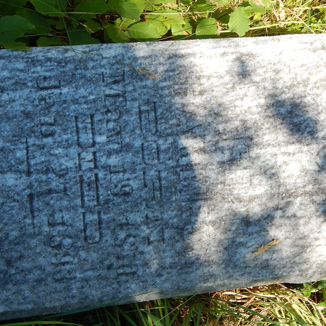 A grave marker on the ground shows a shadow made from a tree.
