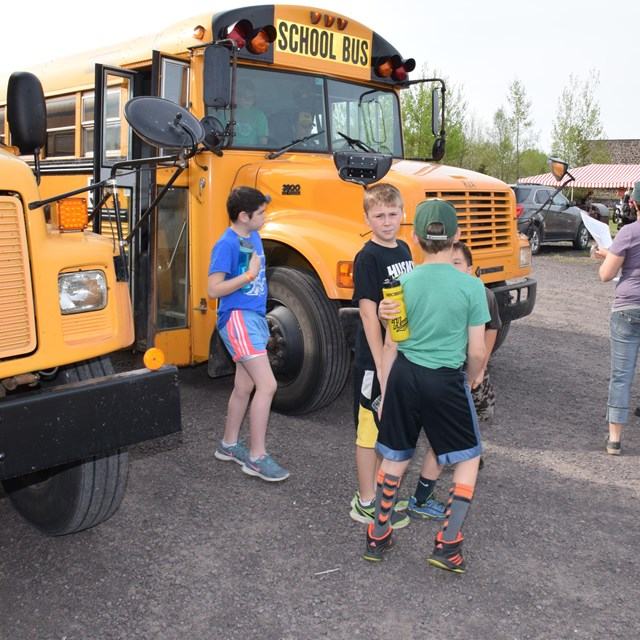 Students walk outside next to a school bus.