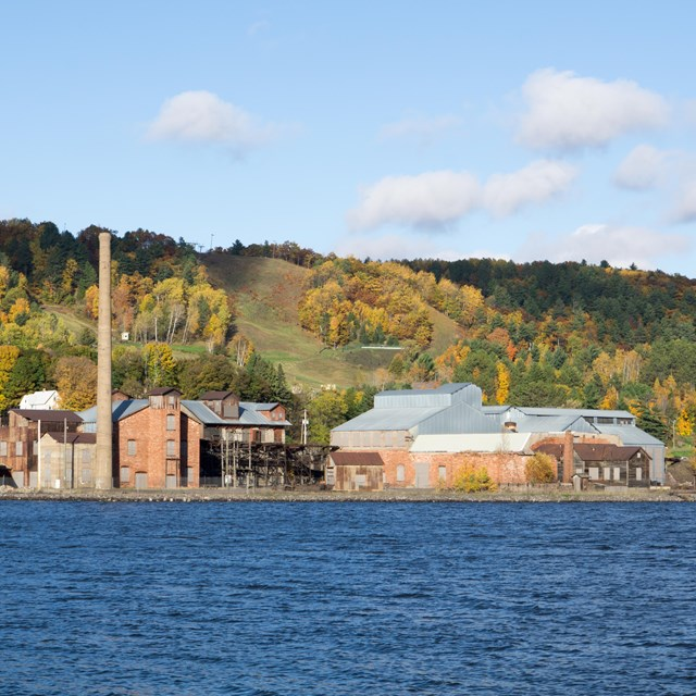 An industrial site with red brick and sandstone buildings sits on the waterfront, with fall foliage