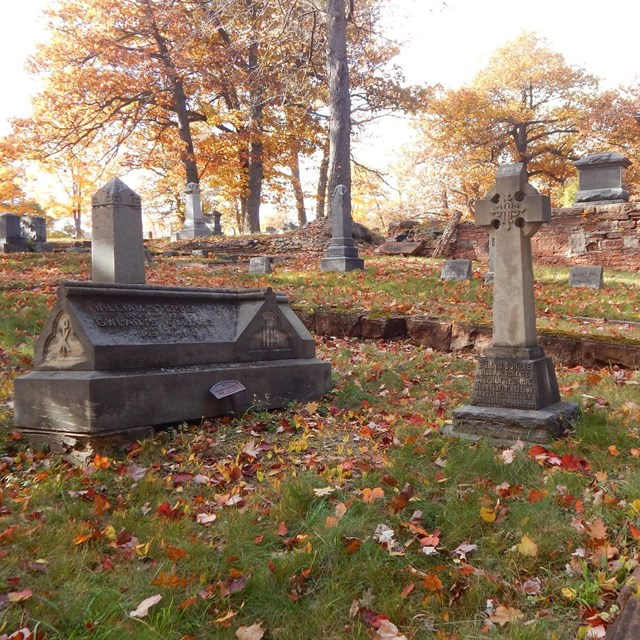 Two grave markers are surrounded by a short masonry fence in a cemetery.