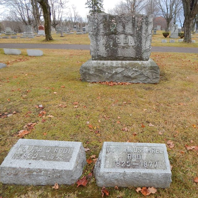 Two small grave markers are in front of a large family grave marker labeled