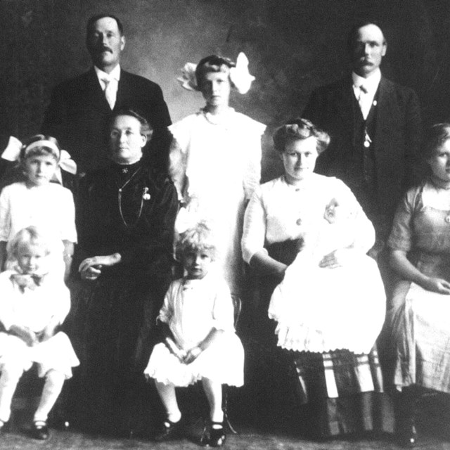 A group of people standing and sitting who are posing for a photograph.