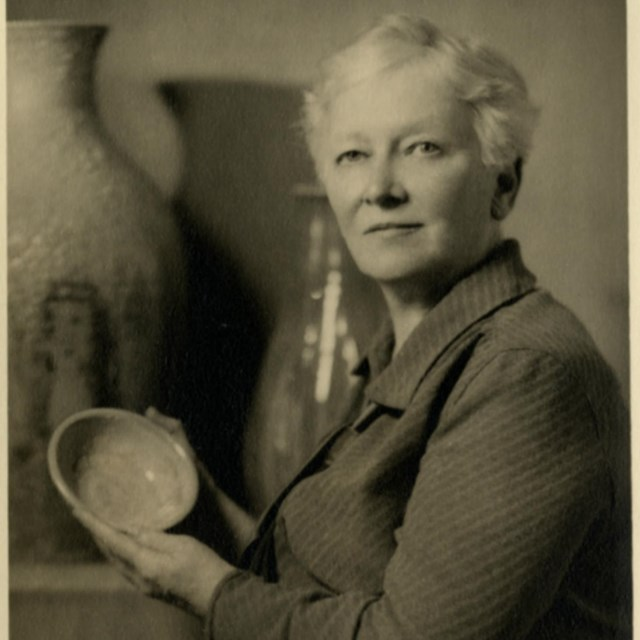 A woman looks at a camera to pose for a photograph while holding a bowl up.